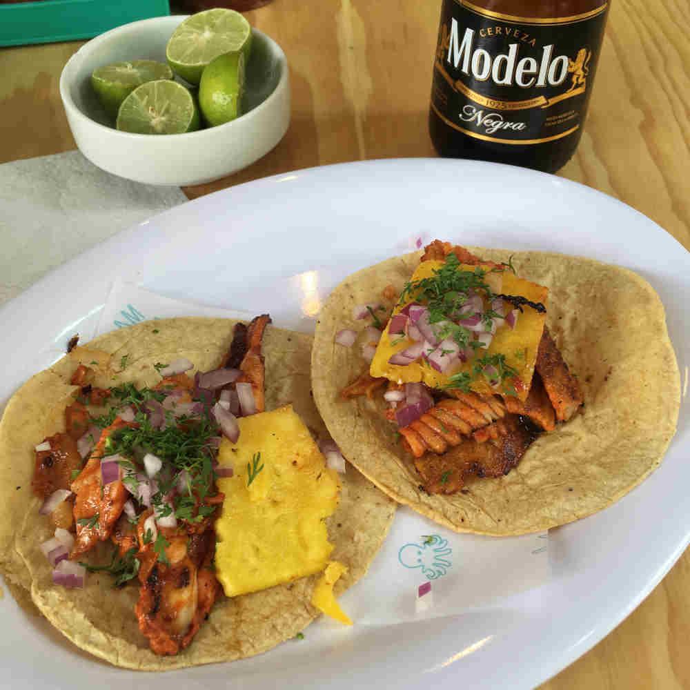 Tacos de pez raya cocinados al pastor con piña, cilantro y cebolla morada, acompañados de una cerveza negra modelo en el restaurante Marea Bonita en la Condesa