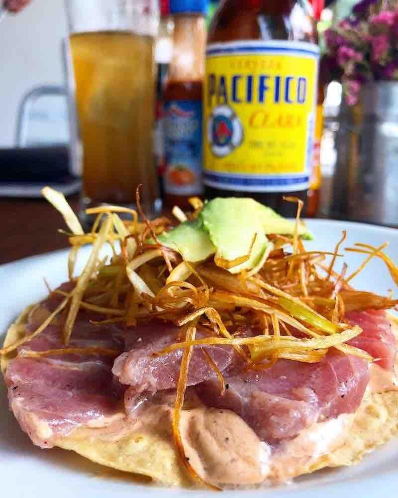 Tostada de atún crudo con mayonesa de chipotle, cebolla tostada y aguacate acompañada de una cerveza pacífico en michelada, del restaurante Mariscos Maviri en la Condesa