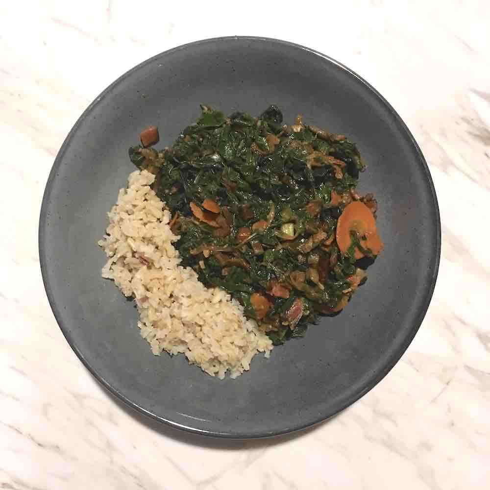 Plato casero de espinacas cocinadas con cebolla, zanahoria y pasas, y arroz integral. Plato de color gris sobre superficie de mármol.